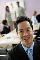 Asian businessman with coworkers in background