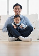 Asian father sitting on floor with baby