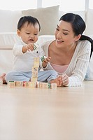 Asian mother and baby playing with blocks on floor