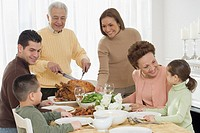 Multi-generational Hispanic family eating at Thanksgiving table