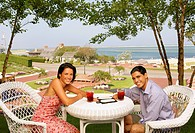 Young couple eating at beach resort