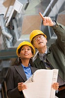 Two businesspeople in hard hats holding blueprints