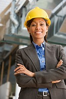 Hispanic businesswoman in hard hat with arms crossed