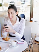 Woman in a caf+ texting on her mobile phone