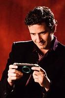 Hispanic man playing hand held video game
