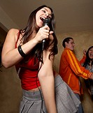 Hispanic woman singing with microphone