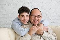 Hispanic grandfather and grandson hugging
