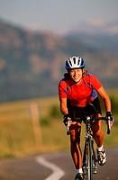 Woman biking on paved road