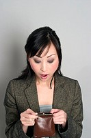 Surprised Asian woman looking through change purse