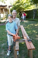 Grandfather and grandson using a saw
