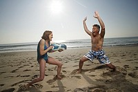 Mature couple playing with watergun at beach