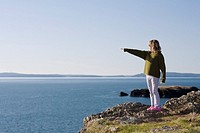 Girl pointing to ocean along cliff
