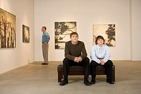 Father with two sons in art gallery