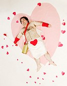 Man in Cupid costume on heart-shaped blanket