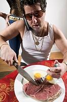 Man eating raw steak and eggs