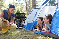 Two sisters smiling at their mother at campsite