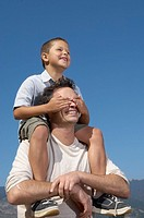 Son riding on fatherÆs shoulders covering his eyes