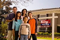 Family standing by suburban house with ´sold´ sign in front yard