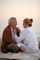 Mature couple sitting together on beach