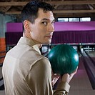 Asian man holding bowling ball
