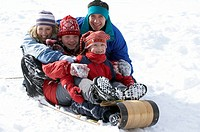 Family sledding down snowy hill