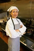 Hispanic female chef standing in kitchen