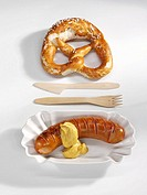 Red sausage with mustard and pretzel