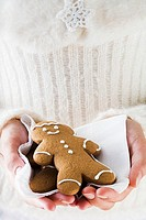 Hands holding two gingerbread men