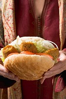 Woman holding flatbread filled with falafel chick-pea balls