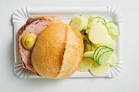 Leberkäse in roll with mustard & potato salad on paper plate