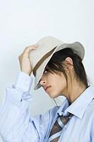 Teen girl wearing shirt, tie and hat, peeking at camera, portrait