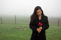 Young woman standing with roses on a cold misty winter morning.