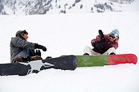 Mid adult couple sitting and throwing snowballs