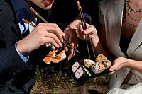 Mid section view of a young couple eating sushi