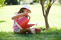 A young girl watering seeds in a plant pot