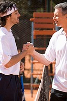 Male tennis players shaking hands over net