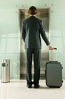 A businessman with a suitcase waiting for the lift