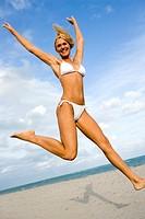 A woman in a bikini jumping on a beach