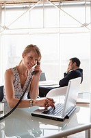 Business woman using laptop while phoning, male colleague in background