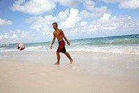 Young man playing football on beach