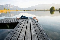 A woman lying down on the pier