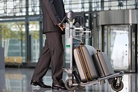 A businessman standing at the airport with his luggage