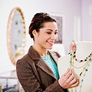 Woman Adjusting Necklace on Display