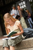 A young student studying on the steps