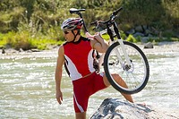 A man carrying his bike across a stream