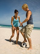 Couple playing football on the beach