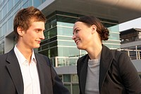 Businessman and a businesswoman looking at each other and smiling