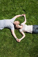 Couple holding hands on lawn