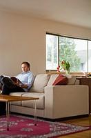 Man reading magazine on sofa