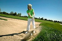 Woman hitting golf ball out of bunker